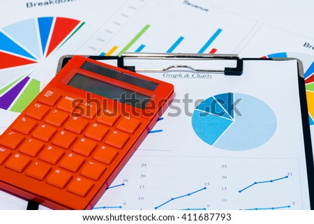 Colorful business charts and calculator with black clipboard - stock photo