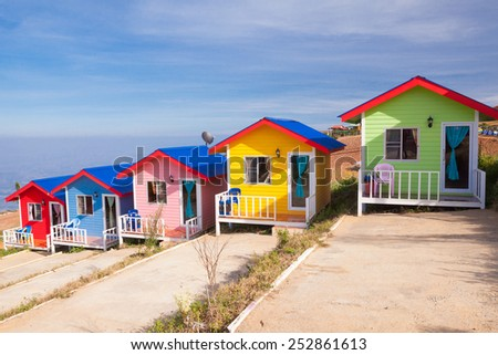 Colorful cabins on the mountain with blue sky - stock photo