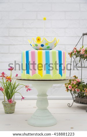 Colorful cake on a cake stand with decorations on wooden table - stock photo