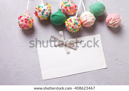 Colorful cake pops and empty tag  on  grey textured  background. Selective focus. Place for text. - stock photo