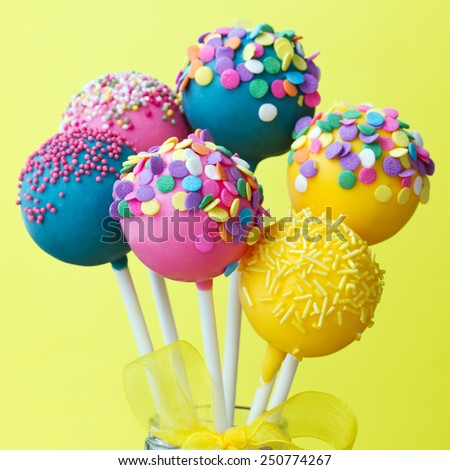 Colorful cake pops on a yellow background - stock photo