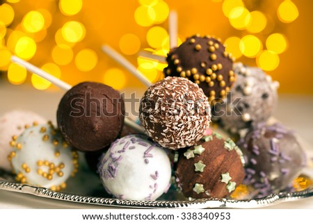 Colorful cake pops on the blurred yellow bokeh background - stock photo