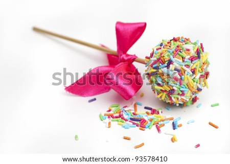 Colorful cake pops with red ribbon, isolated on white - stock photo