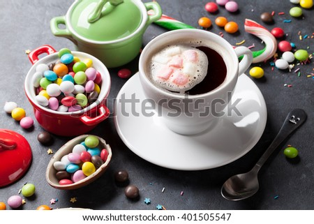 Colorful candies and coffee cup on stone background - stock photo