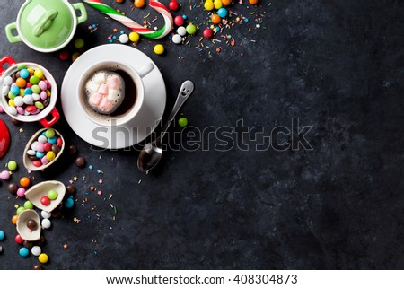 Colorful candies and coffee cup on stone background. Top view with copy space - stock photo