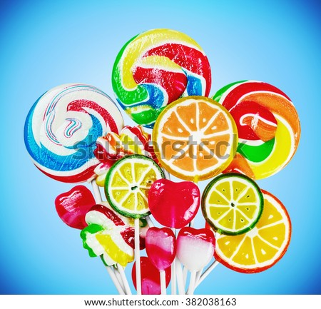 Colorful candies and lollipops on a blue background. focus on large lollipops - stock photo