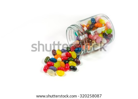 Colorful candies in glass jar isolated on white - stock photo