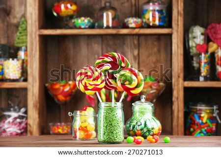 Colorful candies in jars on table in shop - stock photo
