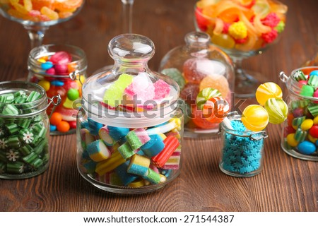 Colorful candies in jars on table on wooden background - stock photo