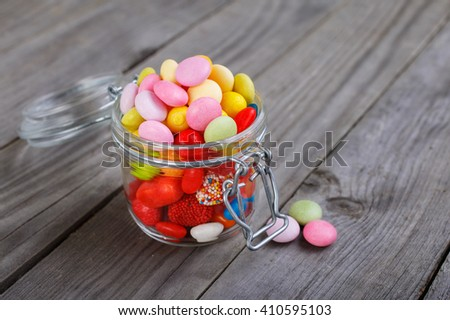 Colorful candies in small jar on the wooden table with copy space - stock photo