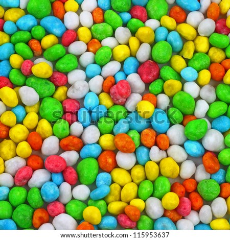 Colorful candies piled on white tablecloth background - stock photo