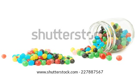 Colorful candy ball sweets falling out of a glass jar, composition isolated over the white background - stock photo
