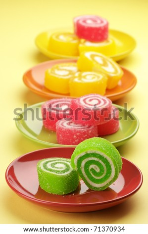 Colorful candy in multicolored saucers on yellow background. - stock photo