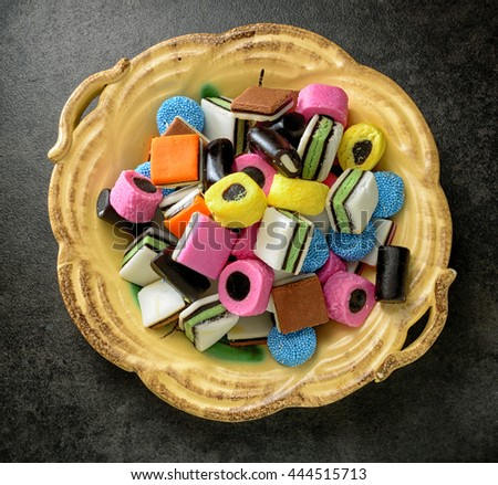 Colorful candy in rustic dish. Liquorice allsorts in many colors and shapes. - stock photo