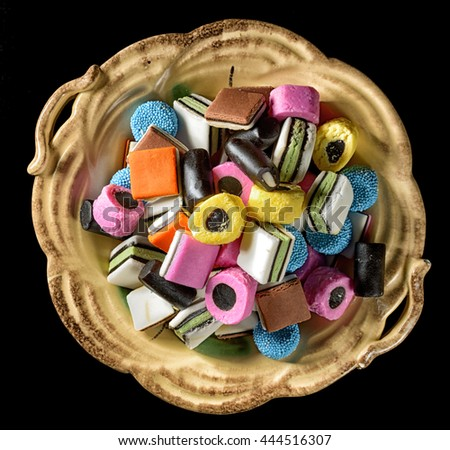 Colorful candy in rustic dish. Liquorice allsorts in many colors and shapes. Filter effects. - stock photo