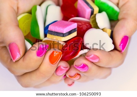 Colorful candy in the hands of women - stock photo
