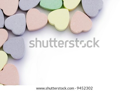 Colorful candy sweet hearts around edges of white - stock photo