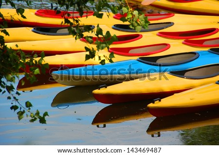 Colorful canoes  and their reflection on water lake pond in a park - stock photo