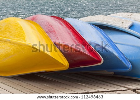 Colorful canoes await paddlers. - stock photo