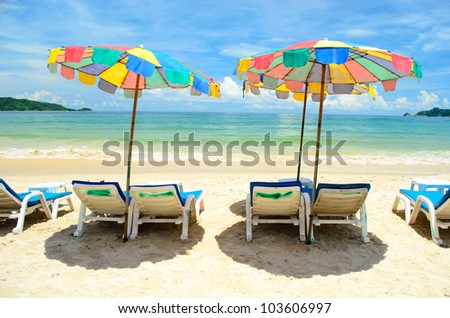 Colorful canvas beds on the beach with beautiful blue sky at phuket - stock photo