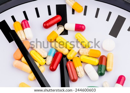 colorful capsules on a clock, symbolic photo for health care, health care reform, reform deadlock - stock photo
