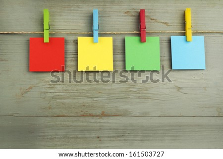 colorful cardboard hanging on a rope over a wooden background - stock photo