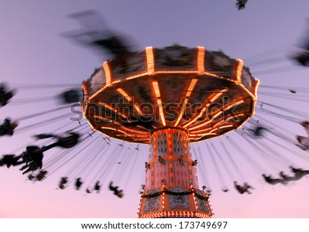 colorful carousel in motion with sundown in background, people enjoy their ride in the carousel  - stock photo