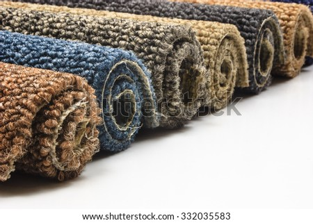 Colorful carpet rolls on white background - stock photo