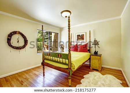 Colorful carved wood bed with high poles and yellow bedding. White fur rug and wall art decorate interior - stock photo