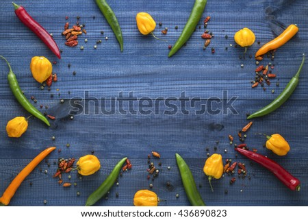 Colorful cayenne chilli peppers, yellow habanero peppers, pepperoncini peppers and color pepper on blue wooden table with copyspace in the centre. Top view. - stock photo