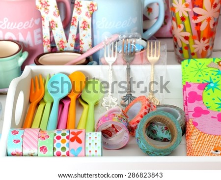 Colorful ceramic and melamine cutlery and dishware in pastel colors - stock photo