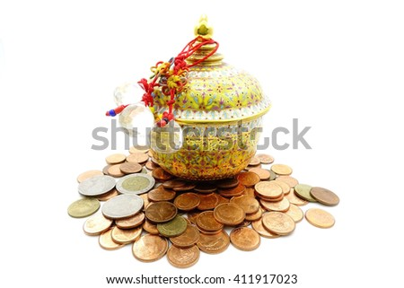 Colorful ceramic ware handcraft bowl over many thai baht coins isolated on white background:Close up,select focus with shallow depth of field. - stock photo