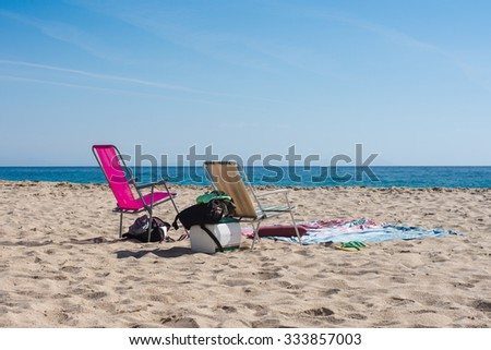 Colorful chairs on golden sand beach. Empty beach. Atlantic ocean. No people.  Blanket, towels, beach equipment, mini fridge. Andalusia, south Spain, Atlanterra beach close to Zahara de los Atunes. - stock photo
