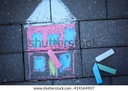 Colorful chalk drawing of house on asphalt surface - stock photo