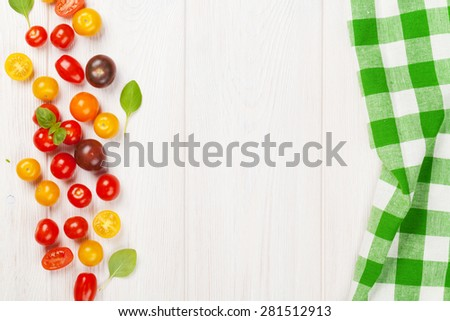 Colorful cherry tomatoes and basil on wooden table background. Top view with copy space - stock photo