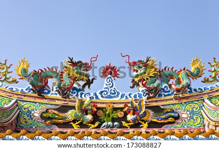 Colorful Chinese dragons fighting on roof, blue sky - stock photo