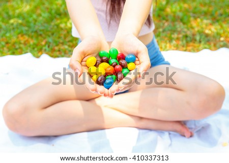 Colorful chocolate candies on hand of pretty women or girl. - stock photo