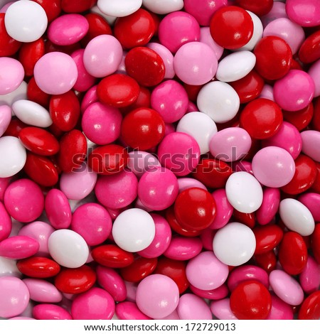 Colorful chocolate Valentine's candy coated in pink, red and white. Background - stock photo