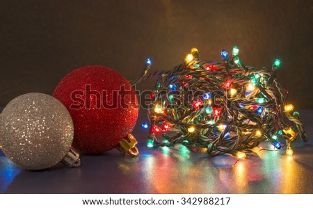 Colorful Christmas lights and shiny baubles - stock photo