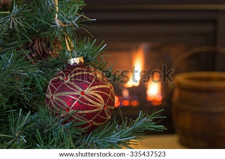 Colorful Christmas ornament hanging on a tree with fireplace in background - stock photo