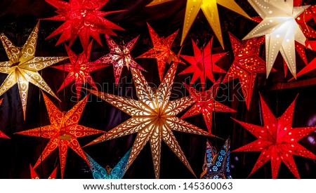 Colorful Christmas stars at a Christmas Market on black - stock photo