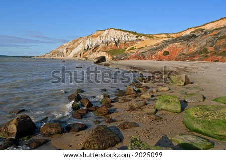 Colorful clay cliffs overlooking a rocky Atlantic seashore at dusk. - stock photo