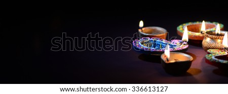 Colorful clay Diya (Lantern) lamps lit during Diwali celebration. Greetings Card Design Indian Hindu Light Festival called Diwali. - stock photo