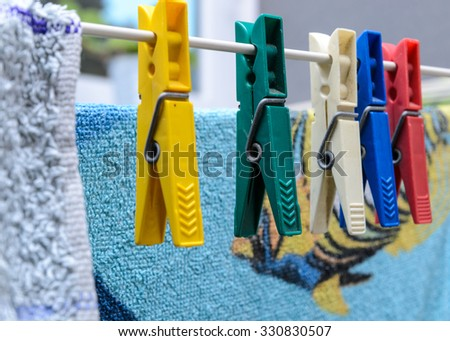 colorful cloth pegs are hanging beside towels - stock photo