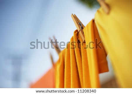 Colorful clothes drying on clothesline. Shallow DOF. - stock photo