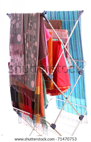 colorful clothes hanged for drying after laundry clothes airer, clothes dryer isolated on white - stock photo