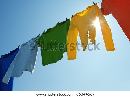 Colorful clothes hanging to dry on a laundry line and sun shining in the blue sky. - stock photo