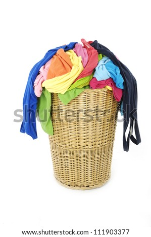 Colorful clothes in a laundry basket on white - stock photo