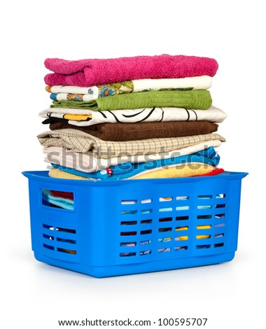 Colorful clothes in a laundry basket on white background. - stock photo
