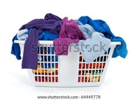 Colorful clothes in a laundry basket on white background. Blue, indigo, purple. - stock photo